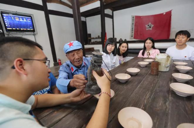 在浙江省温州市永嘉县中国工农红军第十三军军部旧址,老党员为青年团员们讲述革命传统故事。