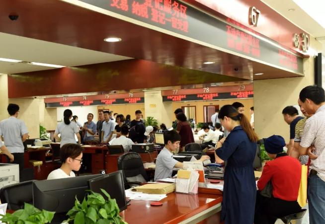 """浙江金华,居民在不动产登记窗口办理""""最多跑一次""""业务。"""