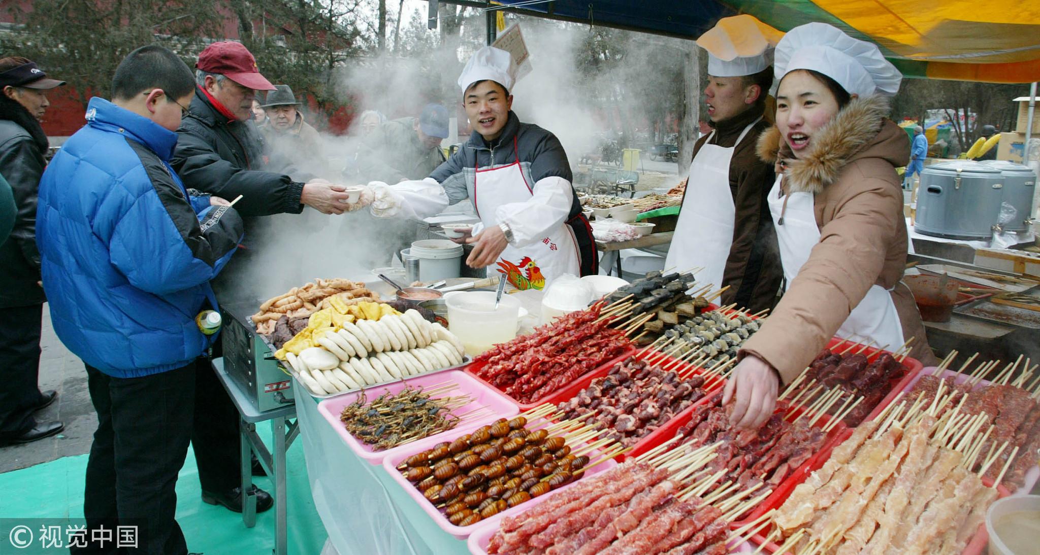 地坛庙会上香气诱人的炸羊肉串和卤煮火烧等小吃